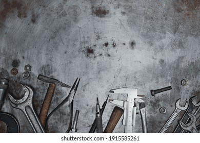 Old hand tools on metal grunge surface, flat lay