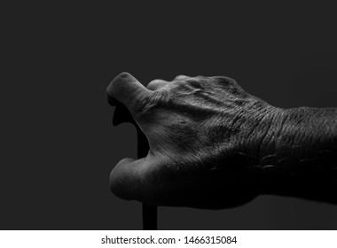 old hand with walking stick in black and white