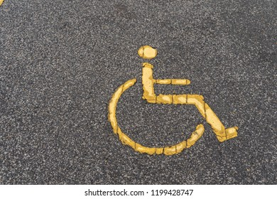 Old Handicapped symbol on parking space, Yellow signs for the disabled on the asphalt parking lot.