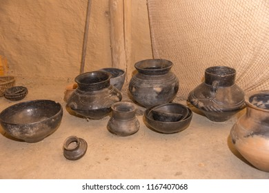 Old handmade clay pots are standing on the floor