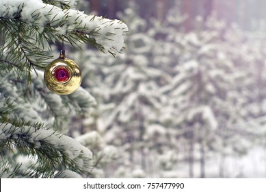 old handmade glass Christmas ornament - bauble with a color cavity - on a living fir against the background of a blurry real winter forest