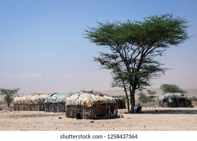Old handmade huts in Samburu/Africa. Man seeking under the tree for shadow in the hot climate. Africa, safari, travel concepts.