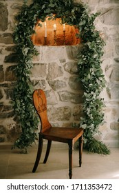 An old handmade wooden chair. Vintage home-made furniture. A chair against the backdrop of an arch of leaves and a stone wall with three burning candles, in the grounds of an old villa