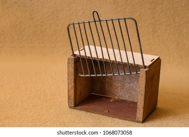 Old handmade wooden (plywood) cage for carrying little birds, white top, opened grate, beige textile background, selective focus, close-up