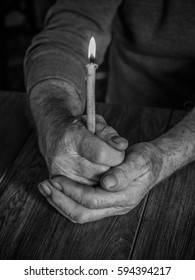 old hands with a candle