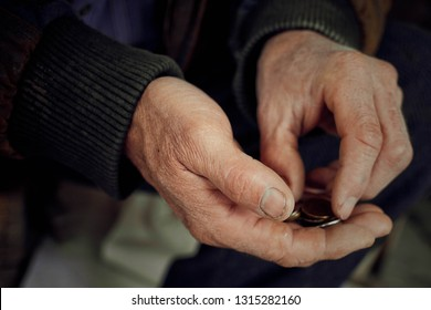Old hands close up consider coins. Concept of poverty.