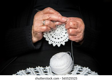 Old hands doing crochet