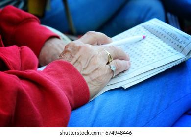 old hands doing crossword puzzle