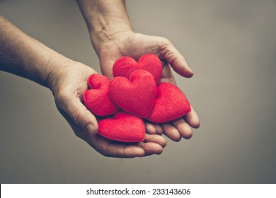 old hands of the female elderly holding small red hearts