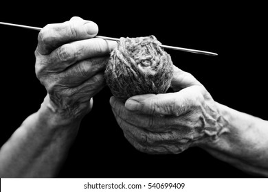 The old hands of grandmother and knitting