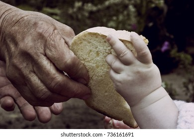 Old hands of a grandmother and a young child with a slice of bread