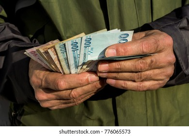Old hands holding some Turkish money.Zoomed hands on his green raincoat.