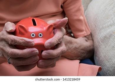 Old hands of pensioner holding piggy bank