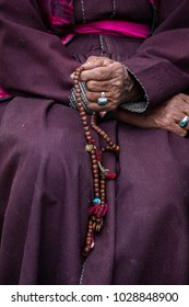 Old hands of a Tibetan woman holding prayer buddhist beads at a Hemis monastery, Leh district, Ladakh, Jammu and Kashmir, north India. Close up