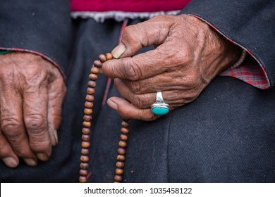Old hands with turquoise ring of a Tibetan woman holding prayer buddhist beads at a Hemis monastery, Leh district, Ladakh, Jammu and Kashmir, north India. Close up