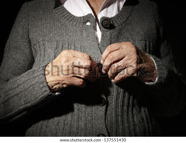 Old hands of an unrecognizable senior woman buttoning her self.