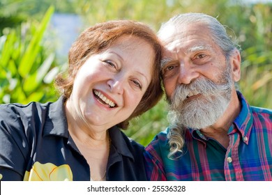 Old happy loving couple showing affection during retirement at their home