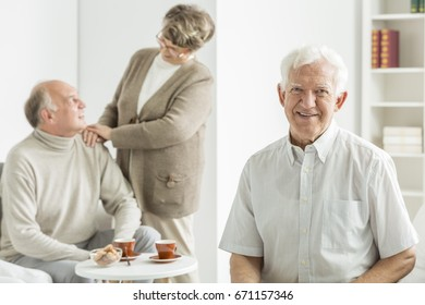 Old happy man smiling during seniors' meeting in common room