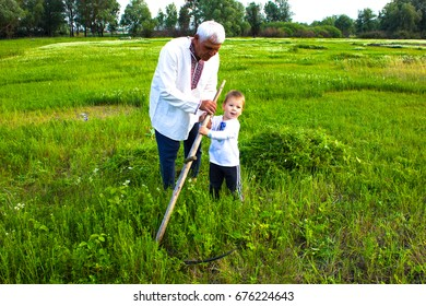 an old happy man in traditional ukranian clothes With grandsonIn embroidered shirt in a meadow