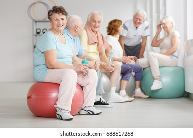Old happy people having a water break during training with exercise balls
