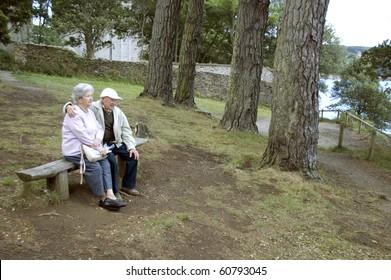 Old happy senior couple sitting on bench