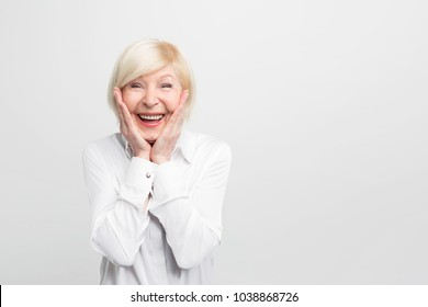 Old but happy woman wears white blouse and showing that she is ery surprised. She has a good luck. Isolated on white background.