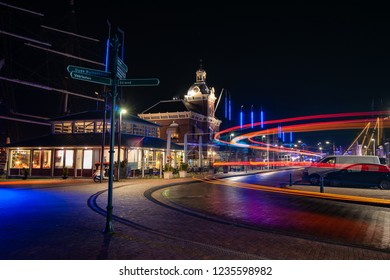 The old harbor building of the Frisian city harlingen in the north of the Netherlands. Classic architecture in an old seaport with atmospheric lighting and the trails of car lights and buses