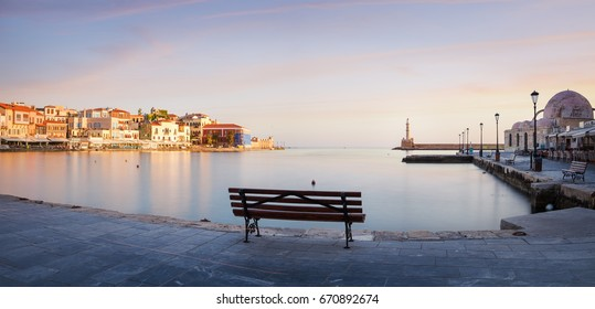 Old harbor of Chania with bench and lighthouse at sunset, Crete, Greece