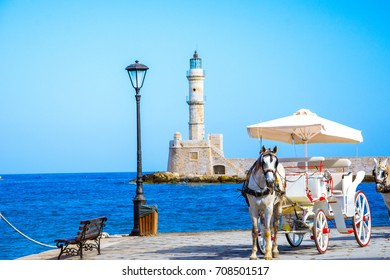 The old harbor of Chania with horse carriages and lighthouse, Crete, Greece.