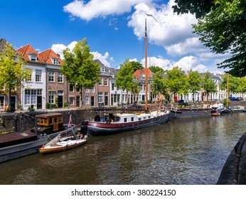 The old harbor in Den Bosch the Netherlands, with boats anchored at the quay and medieval houses on a summer day