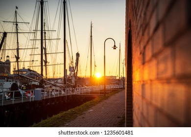 The old harbor of Harlingen in the Netherlands. Old sailboats and cargo ships with sails and masts wait for the lock to the Wadden Sea and the North Sea in the north of the Netherlands