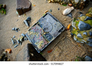 Old hard drive washed ashore on a beach.