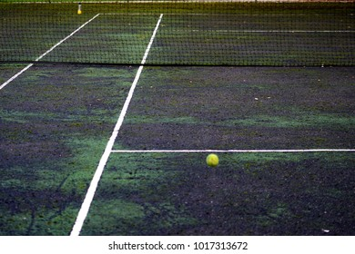 An old hard tennis court with ball and net
