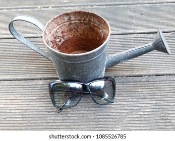 old hard used watering can with sunglases