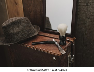 Old hat and shaving equipment on an old suitcase in a retro interior. Texture effect and film grain add. Not camera noise. Cinematic look. Low Light.