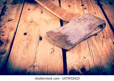 An old hatchet axe with a wooden handle and wear marks sits on a rough timber background with retro style filter effect
