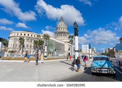 Old Havana, Cuba. February 2018 - Classic vintage American taxi cars pass in front of the classic architecture of the El Capitolio building on the streets of Habana Vieja.