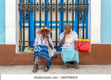 Old Havana, Havana, Cuba-March 27, 2019: Old ladies smoking cigars. Two senior women pose for tourists in exchange for tips. The place is a Unesco World Heritage Site