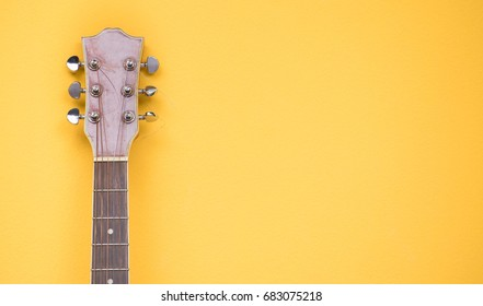 old head acoustic guitar on yellow pastel color background.concept for musical instrument background