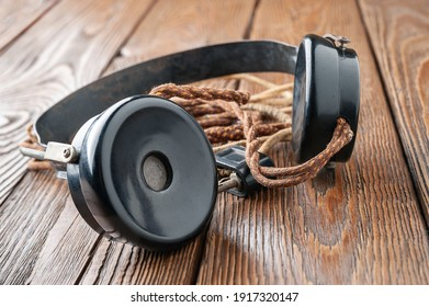 Old headphones. Vintage headphones with a cloth wire on a wooden background. The concept of ancient radio engineering. Selective soft focus.
