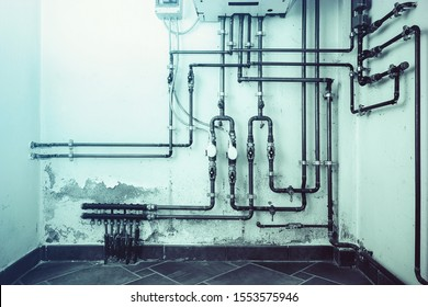 Old heat pipes room. Dramatic picture of a boiling room with damaged walls cause the mold