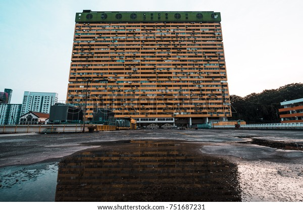 Old high rise apartment block the Peoples Park Complex in Singapore reflecting in a puddle in front of it.