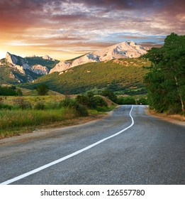 Old highway against mountains and a cloudy sky at the sunset