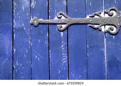 Old hinge on blue wooden gate