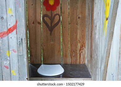 Old hippie wooden outhouse with red flower painting