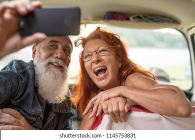 An old hipster couple sitting in a camper van doing a selfie with a phone. he is tattooed and he wears a white beard, she has red hair