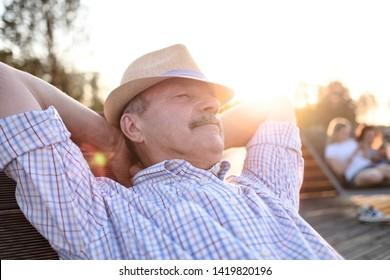 Old hispanic man sits on bench, smiling, enjoying summer sunny day.