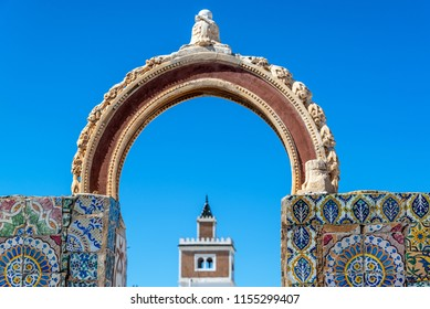 Old historic colorful arch with a mosque in the background in Tunis, Tunisia