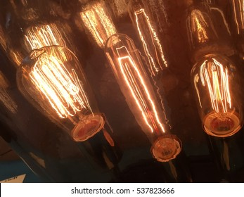 Old Historic Decorative antique Thomas Edison style light bulbs Evolution of Technology and Light with these three light bulbs dark diagonal