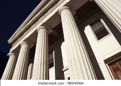 Old Historic Federal Style Architecture Capitol Courthouse Building wtih White Column Pillars Bright Early Moning Sunlight Against Blue Sky